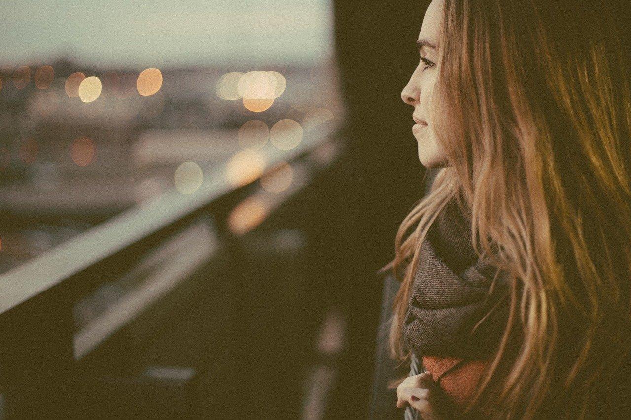 verträumte Frau sitzt am Fenster